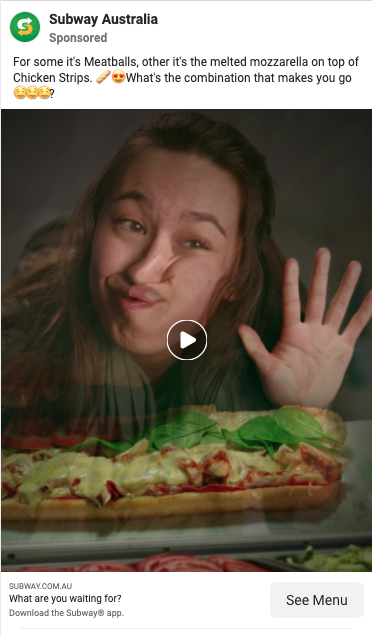 Ad from subway showing girl stuck to window looking at cheesy meatball sandwich