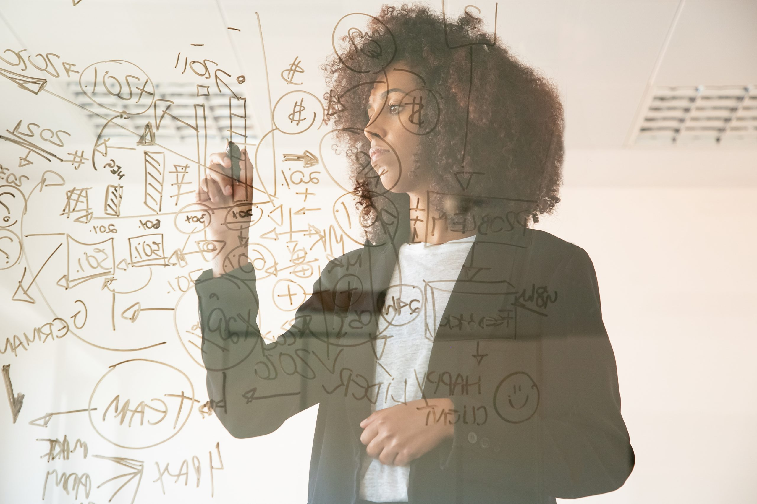 Focused woman of African ethnicity drawing on whiteboard