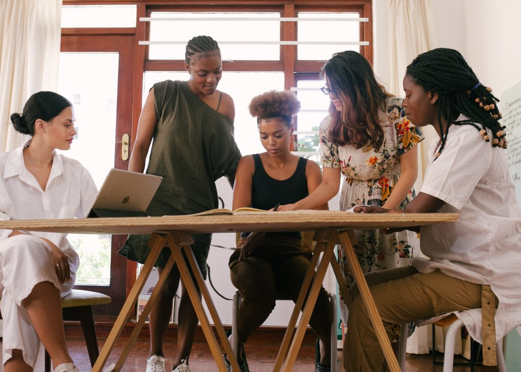 Group of females of different ethnicity sitting at wooden table collaborating and working together