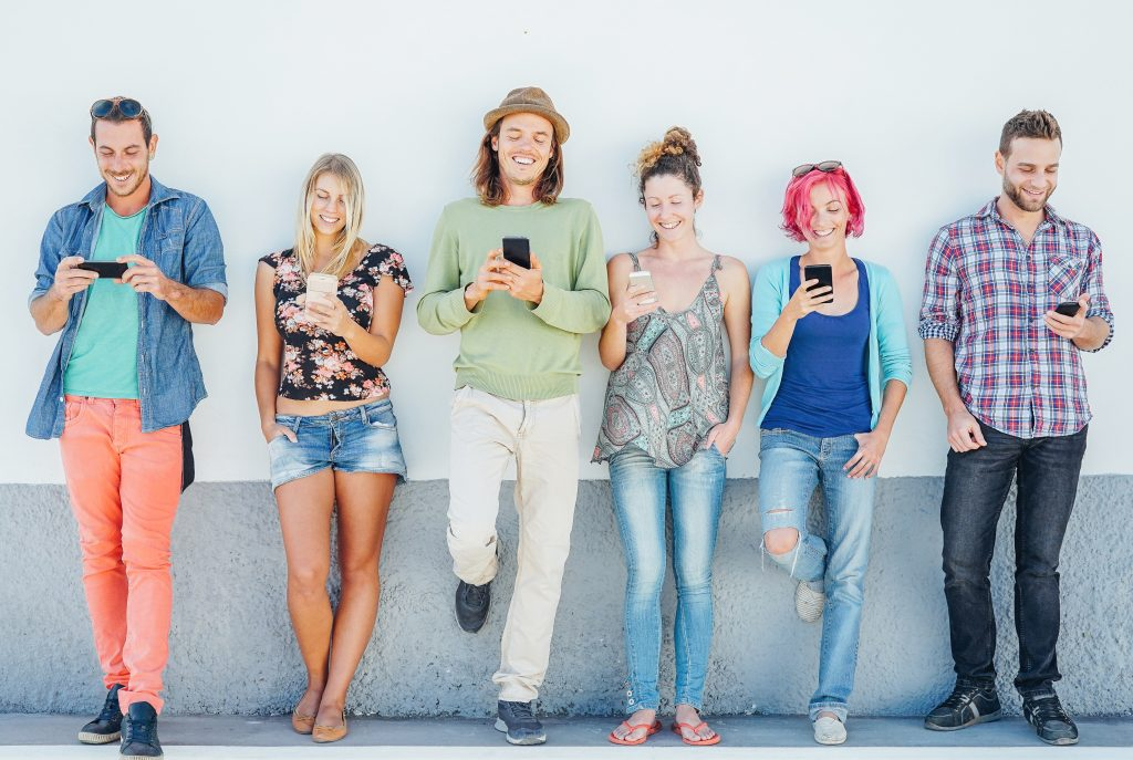 Group of young people watching on their mobile phones wearing colourful clothes leaning agains a grey wall