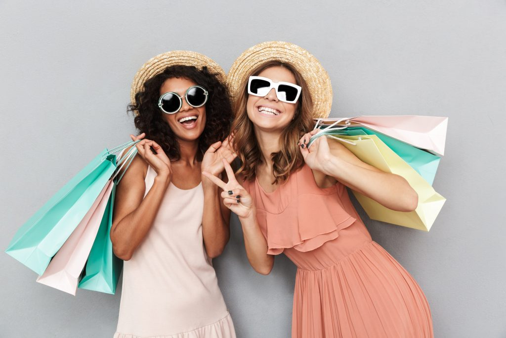 Two young girls in peach dresses wearing sunglasses and beach hats doing peace sign and laughing into camera holding several shopping bags