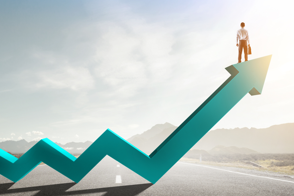Office man standing on top of arrow showing growth