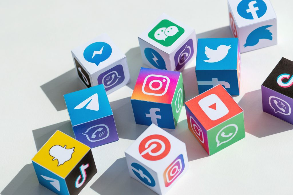 Colourful blocks with social media icons printed on like snapchat, instagram, twitter, facebook, pinterest, whatsapp, tiktok