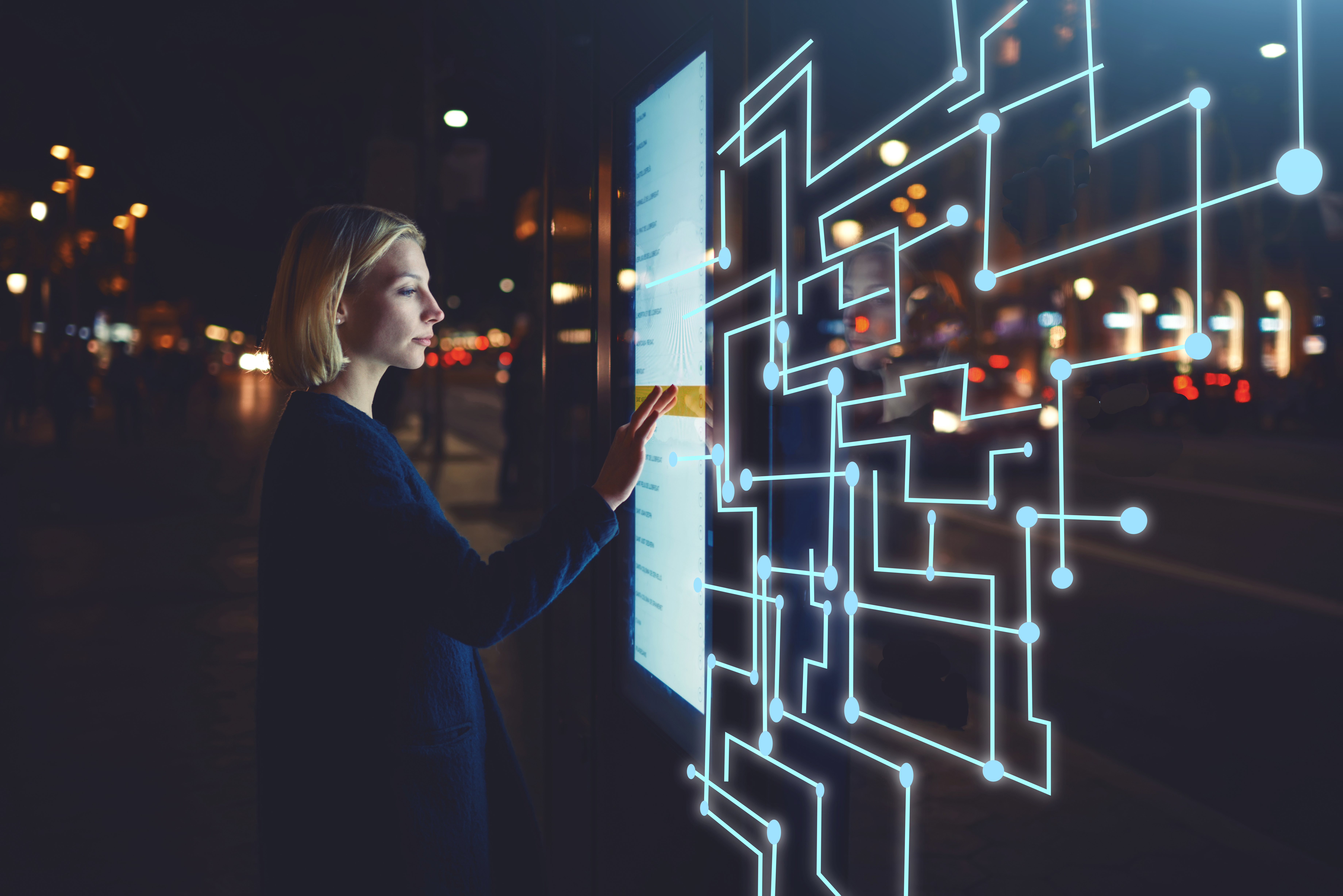 Woman with blonde bob in navy cardigan outdoors at night time scrolling through virtual touch screen